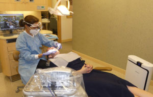 patient receiving flossing from dental assistant